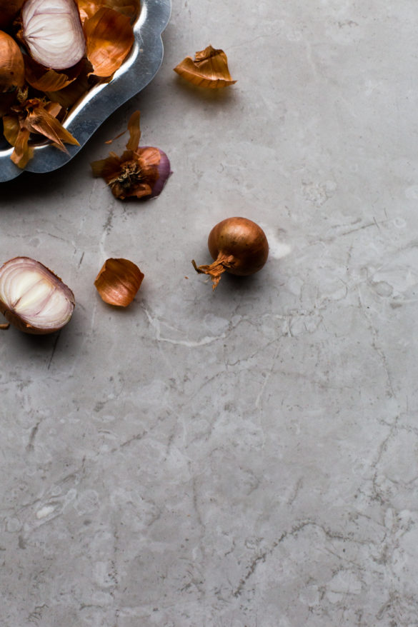 Tray of peeled shallots on marble table