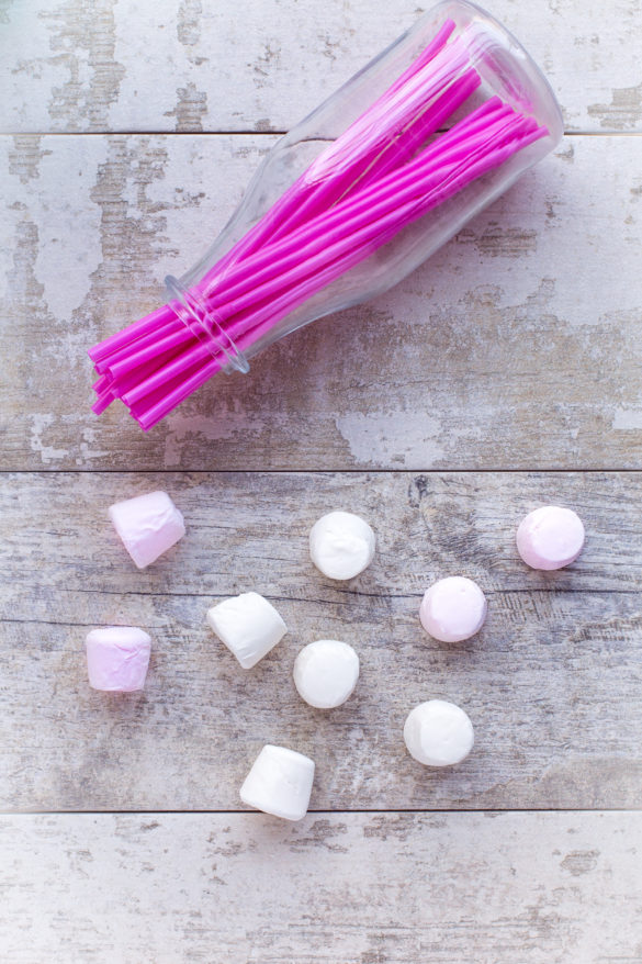 pink and white marshmallows and party straws on table