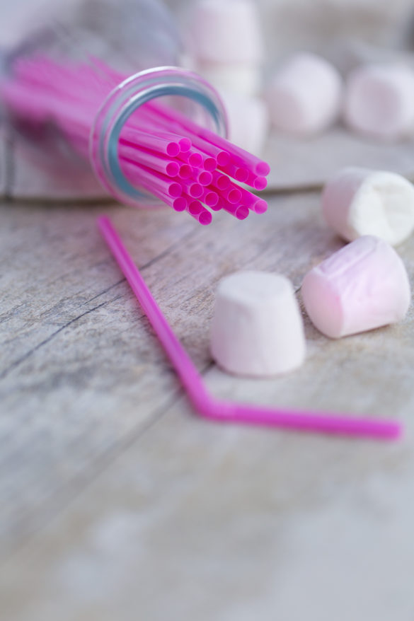 Pink party straws and marshmallows on table