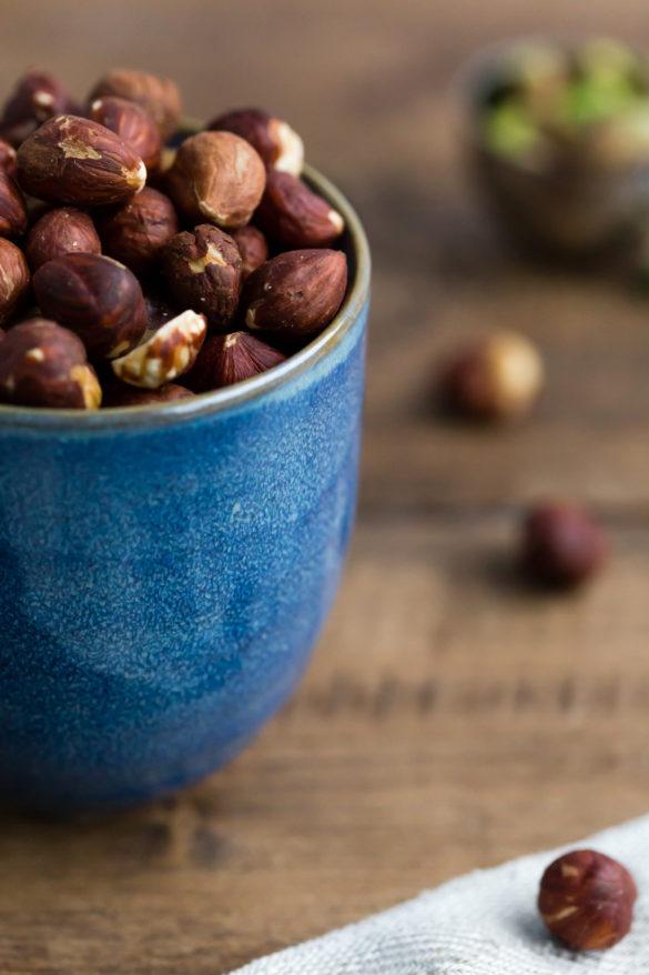 Hazelnuts in Blue Pot on Rustic Wooden Table