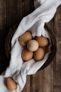 Eggs in wooden bowl with white cloth