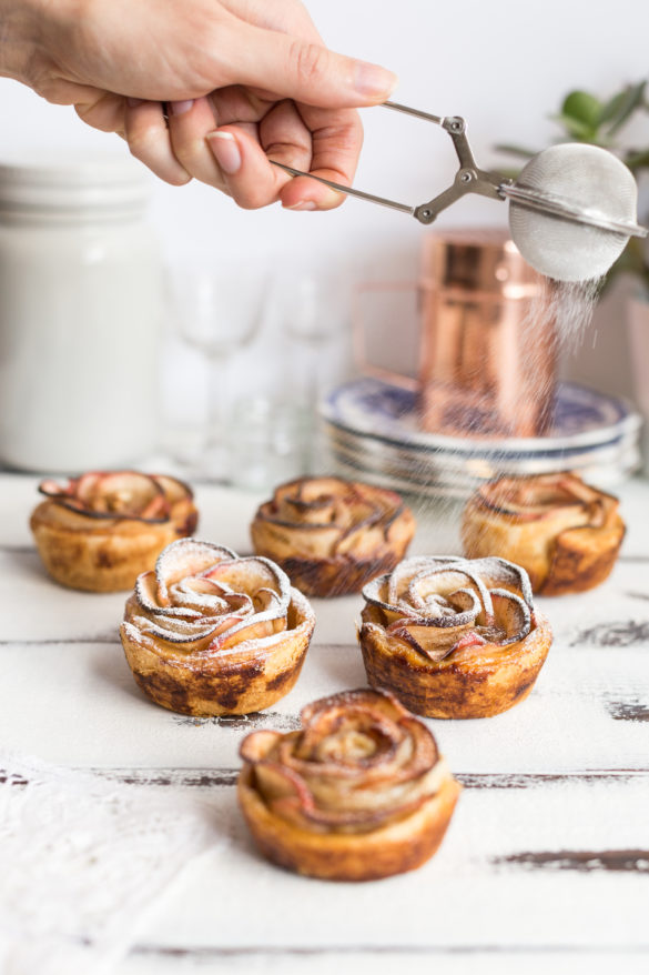 Hand sprinkling icing sugar over apple rose tarts