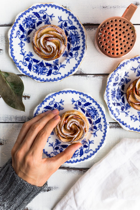 Hand taking apple rose tart from vintage plate