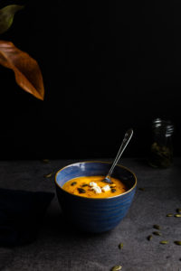 Butternut squash soup in blue bowl on black background