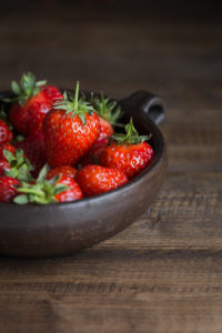 Strawberries in rustic bowl on table