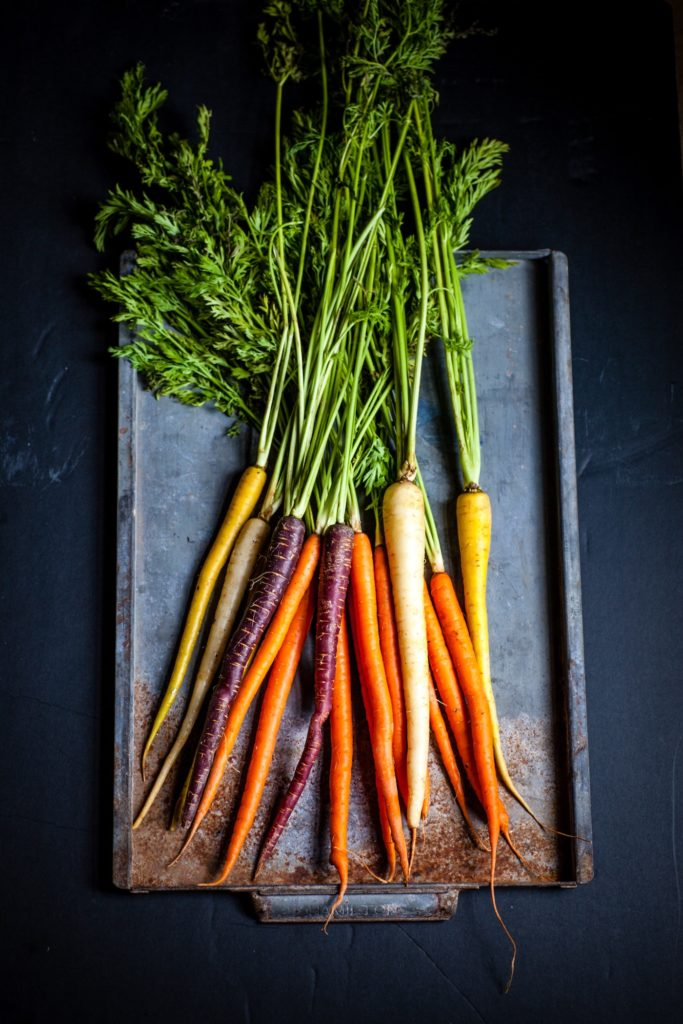fresh bunch of colourful carrots on tray