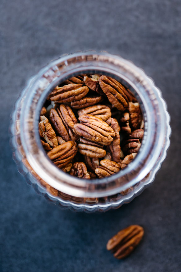 pecan nuts in glass jar on black table